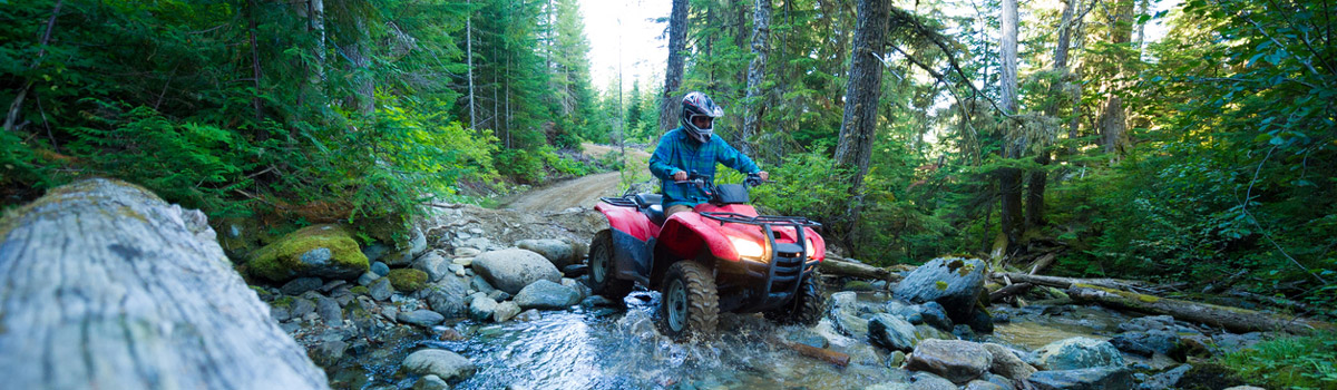 ATV enthusiast enjoying a ride through the woods in the Laurentians knowing he is well insured through DCP Creneau Insurance Firm